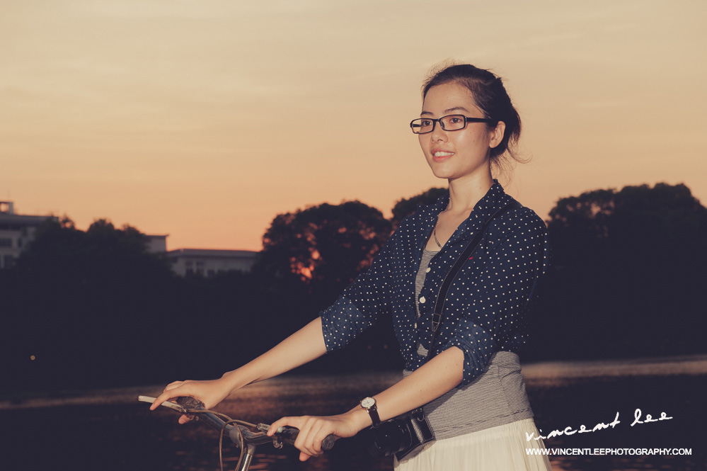 Vietnamese modern looking girl with her bicycle at Ho Kiem Lake - Hanoi
